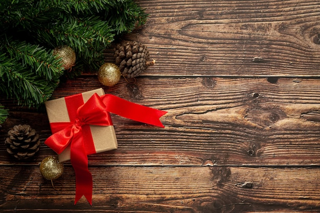 Box of present with red ribbon bow on wooden background Free Photo