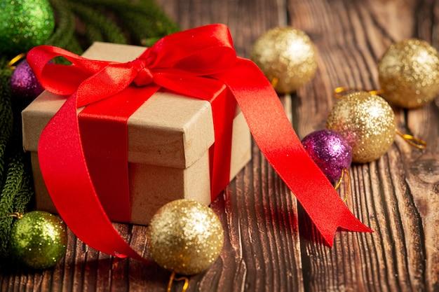 Scatola del presente con fiocco di nastro rosso su fondo in legno Foto Gratuite