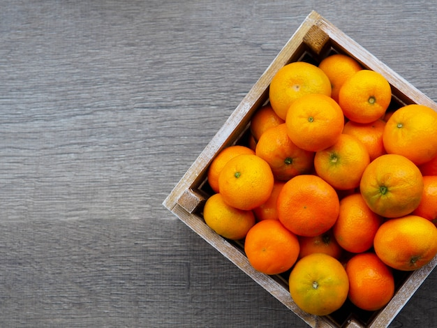Box of tangerines on wooden table Premium Photo