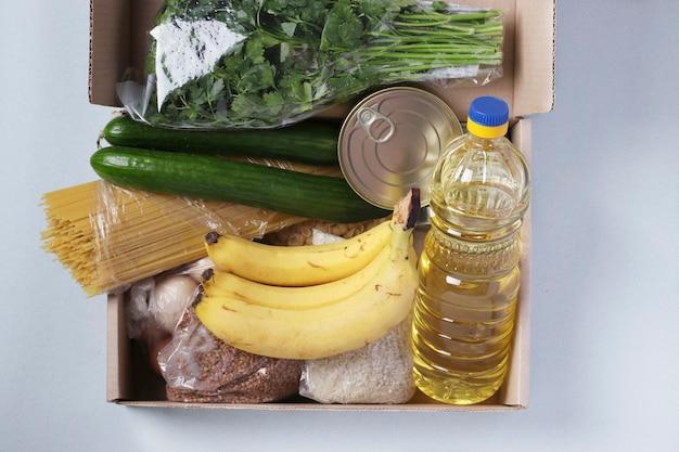 水色の食料品が入った箱。米、そば、パスタ、缶詰、バナナ、きゅうり、卵、植物油。フードデリバリー、寄付、トップビュー Premium写真