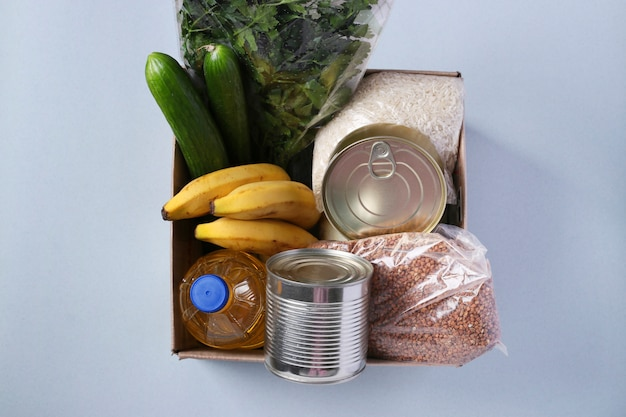 Box with food supplies stock. rice, buckwheat, pasta, canned food, banana, cucumbers, eggs, vegetable oil. Premium Photo