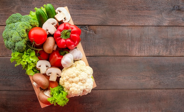 Box with vegetables on wooden background Premium Photo