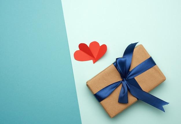 Коробка, завернутая в коричневую бумагу и перевязанная голубой шелковой лентой с бантом, подарок, вид сверху, Premium Фотографии