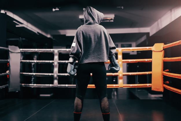 Boxer girl with hoodie and boxing gloves on standing in ring with backs turned. Premium Photo