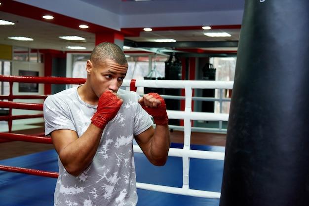 Boxer hitting a huge punching bag at a boxing studio. boxer training hard. Premium Photo