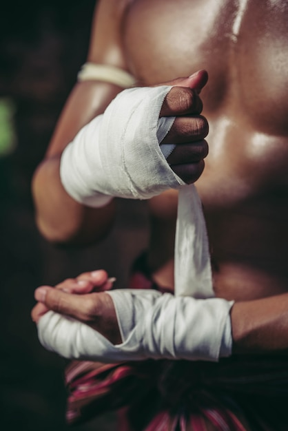 The boxer sat on the stone, tied the tape around his hand, preparing to fight. Free Photo