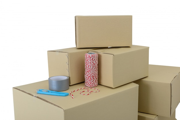 Boxes in different sizes stacked boxes, adhesive tape, rope and cutter isolated Premium Photo