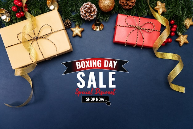 Boxing day sale with christmas present and xmas decoration on blue Premium Photo