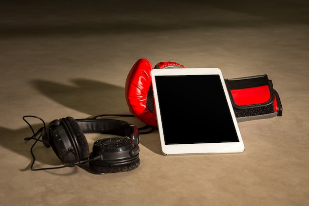 Boxing glove with tablet and headphone for listen music on boxin Premium Photo
