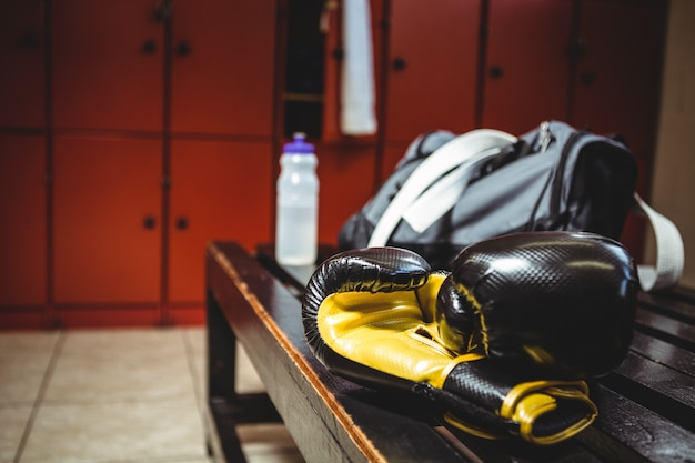 Boxing gloves on bench in locker room Free Photo