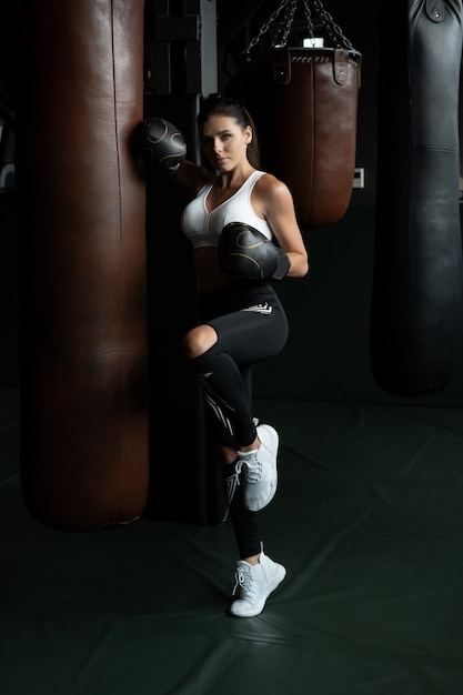 Boxing woman posing with punching bag, on dark background. strong and independent woman concept Free Photo