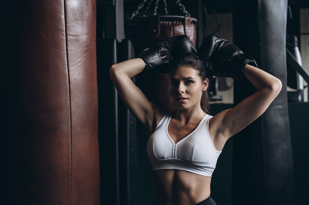 Boxing woman posing with punching bag, on dark . strong and independent woman concept Free Photo