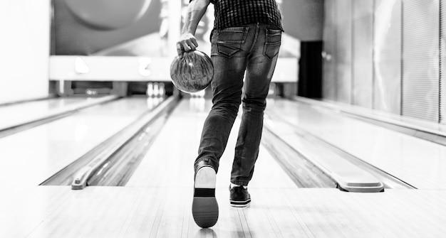 Ragazzo che sta per lanciare un concetto di hobby e tempo libero della palla da bowling Foto Gratuite