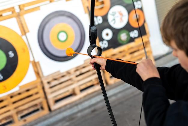 Boy aiming with a training bow at a bullseye at a fair. Premium Photo