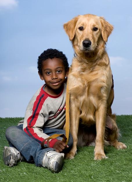 少年と青い空を背景に草の上に座っているゴールデン・リトリーバー Premium写真