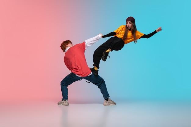 Мальчик и девочка танцуют хип-хоп в стильной одежде на градиентный фон в танцевальном зале в неоновом свете. Бесплатные Фотографии