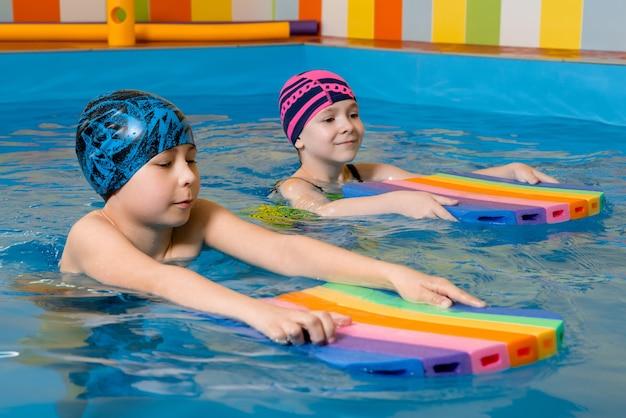 Мальчик и девочка в купальнике используют поролоновую подушку, чтобы поплавать в бассейне Premium Фотографии