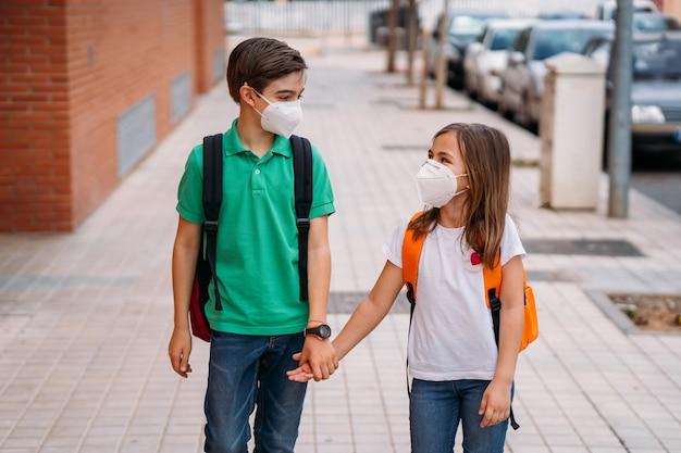 バックパックとマスクを持つ男の子と女の子がコロナウイルスのパンデミックで学校に行きます Premium写真