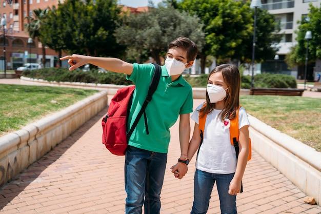 男の子と女の子のバックパックとマスクコロナウイルスのパンデミックで学校に行く Premium写真