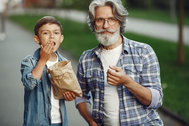Мальчик и дедушка гуляют по парку. старик играет с внуком. люди едят попкорн. Бесплатные Фотографии