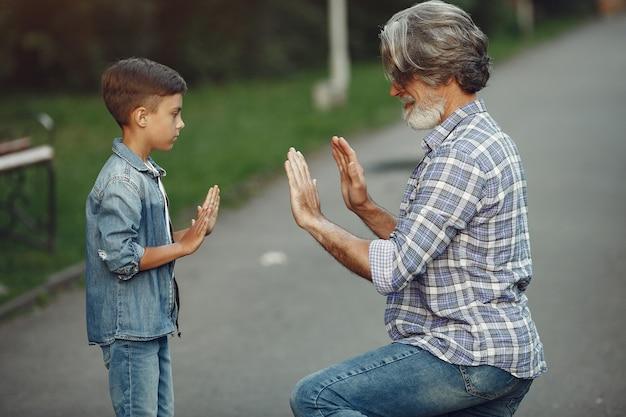 Мальчик и дедушка гуляют по парку. старик играет с внуком. Бесплатные Фотографии