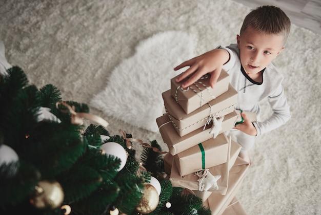 크리스마스 선물의 스택을 준비하는 소년 무료 사진