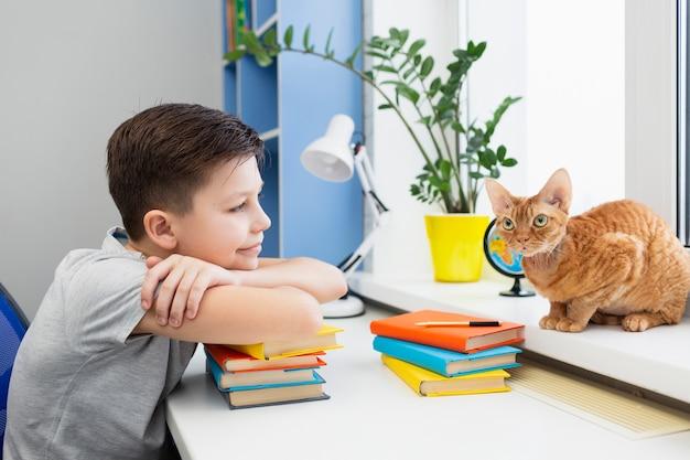 書籍のスタックを持つテーブルで少年 無料写真