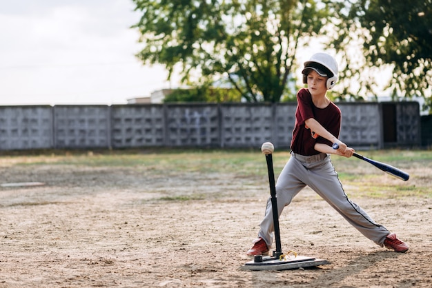 A boy, a baseball player, hits a ball with a baseball bat Premium Photo