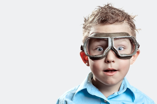 Boy in blue shirt and pilot glasses on light Premium Photo