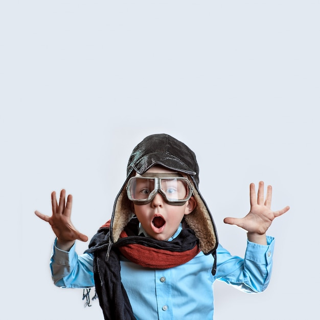 Boy in a blue shirt, pilot's glasses, hat and scarf raised his hands Premium Photo