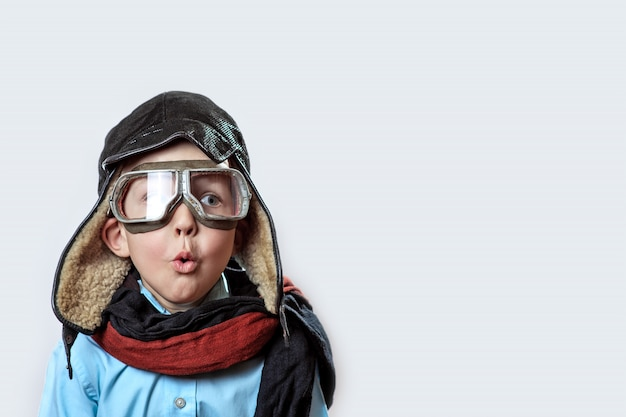 Boy in a blue shirt, pilot's glasses, hat and scarf Premium Photo
