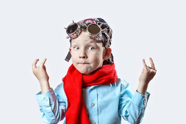 Boy in blue shirt, red scarf, biker glasses and bandana on light background Premium Photo