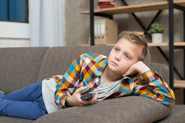 Boy bored on couch Free Photo