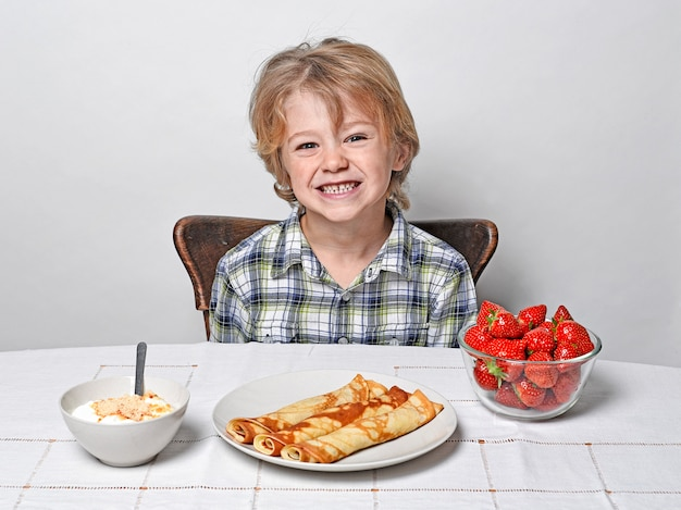 Boy at breakfast table eating pancakes and strawberries Premium Photo