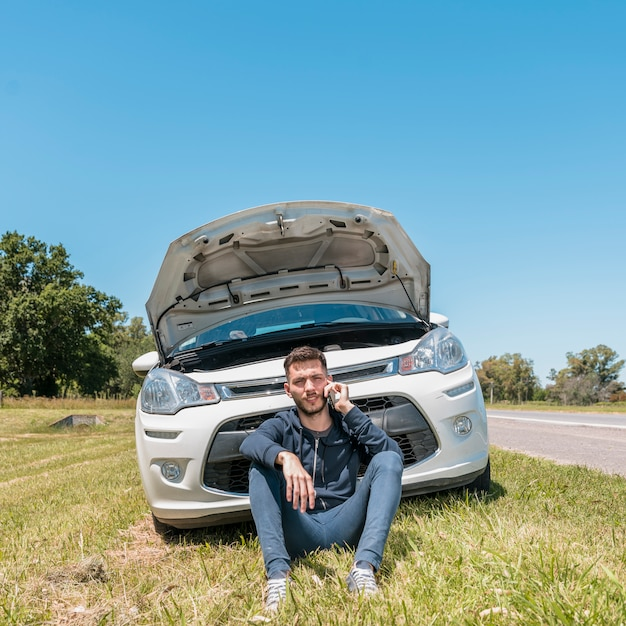 Boy calling next to broken down car Free Photo