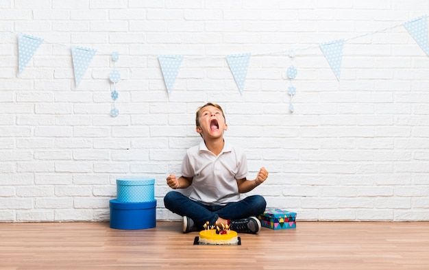 Boy celebrating his birthday with a cake annoyed angry in furious gesture Premium Photo