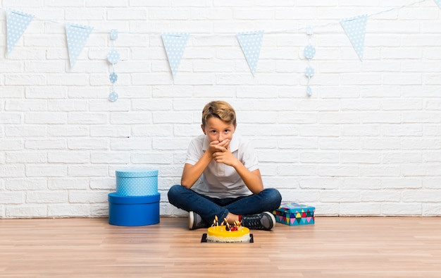 Boy celebrating his birthday with a cake covering mouth with hands Premium Photo