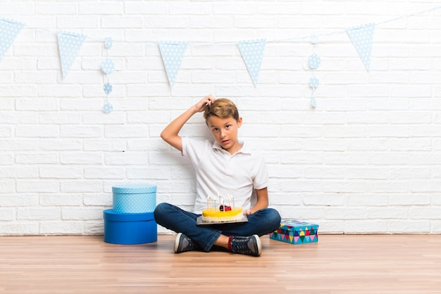 Boy celebrating his birthday with a cake standing and thinking an idea Premium Photo
