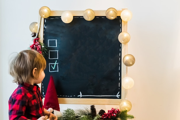 A boy checking options on a blackboard with copyspace Premium Photo