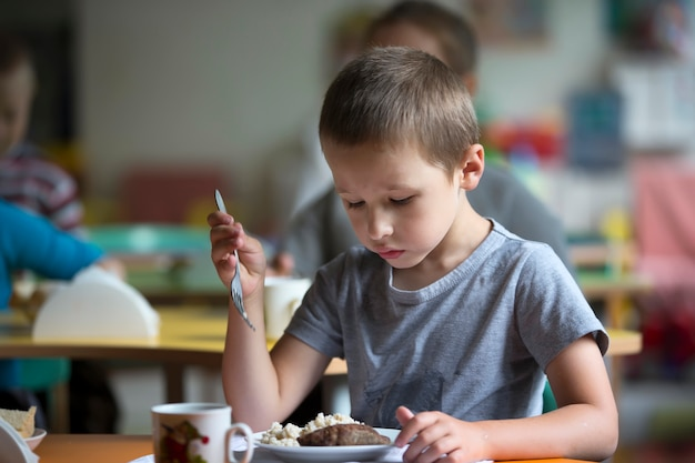 Boy child does not want to eat. bad appetite. eating in kindergarten Premium Photo