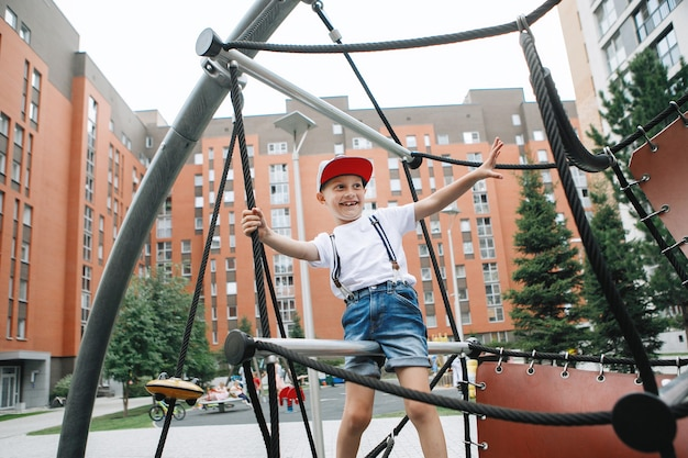 Boy climbs on the rope equipment at the city playground Premium Photo
