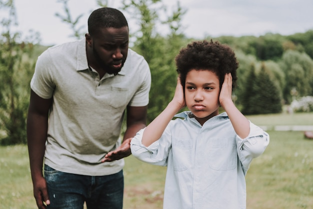 Boy closes ears and turned away from father. Premium Photo