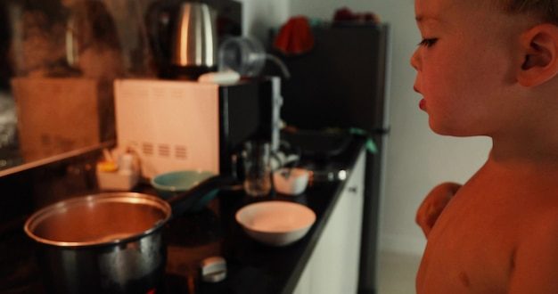 Boy cooking by herself at home. child gets a hot fork out of the pan and burns Premium Photo