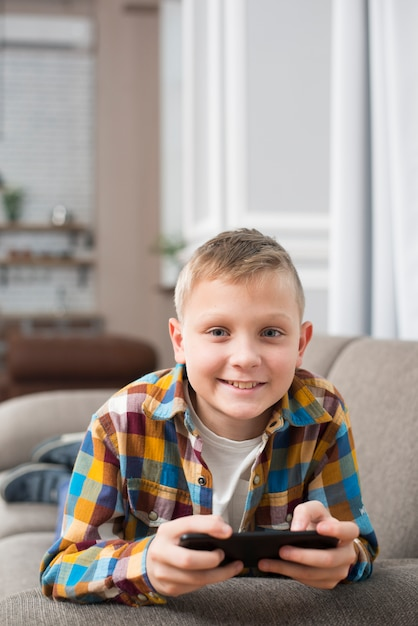 Boy on couch using smartphone Free Photo