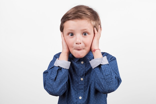 Boy covering ears Free Photo