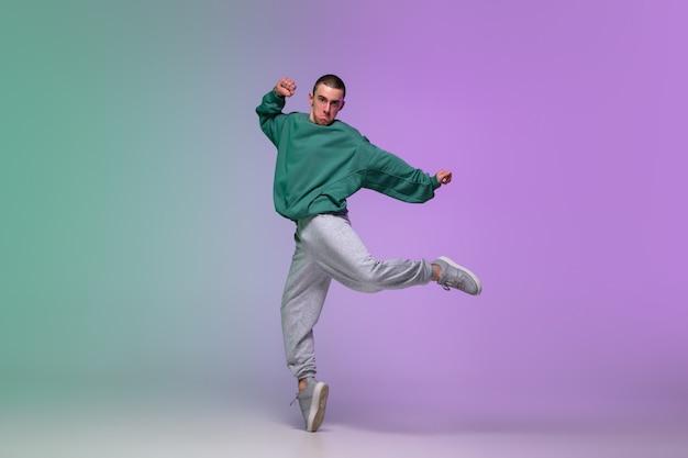 Мальчик танцует хип-хоп в стильной одежде на градиентный фон в танцевальный зал в неоновом свете. Бесплатные Фотографии