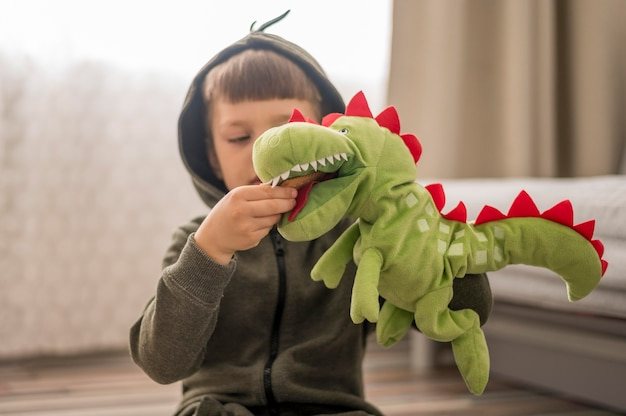 Boy in dinosaur costume playing at home Free Photo