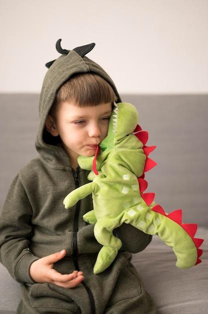 Ragazzo in costume dinosauro giocando Foto Gratuite
