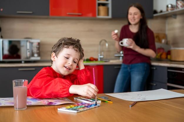 母がお茶やコーヒーを飲みながらキッチンで描く少年 Premium写真