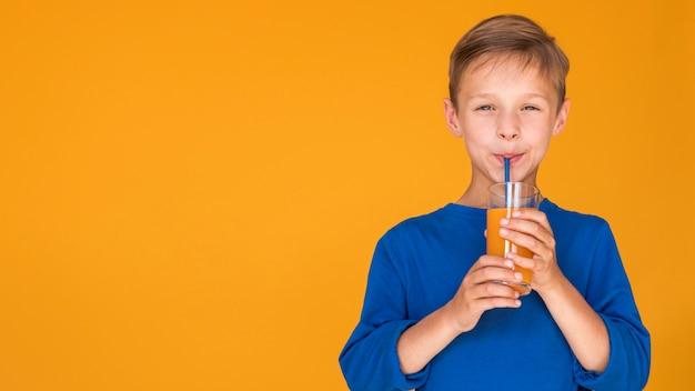 Boy drinking orange juice with copy space Free Photo